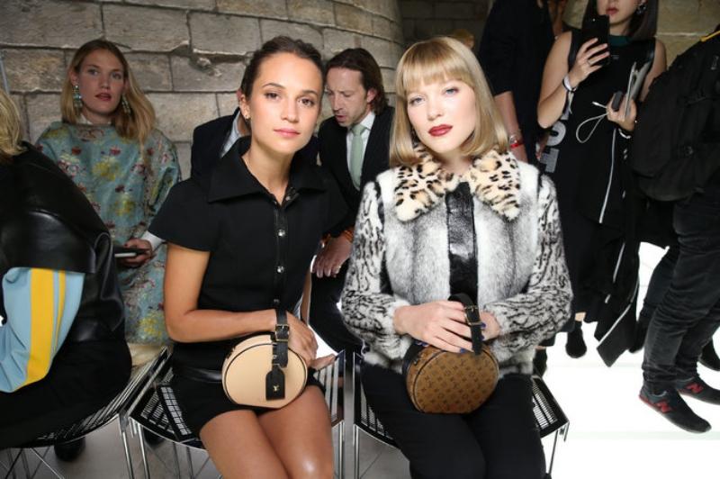 Alicia Vikander (trái) và Léa Seydoux ngồi hàng đầu show diễn Xuân Hè 2018 của Louis Vuitton cùng với hai phiên bản Petite Boite Chapeau trong tay.