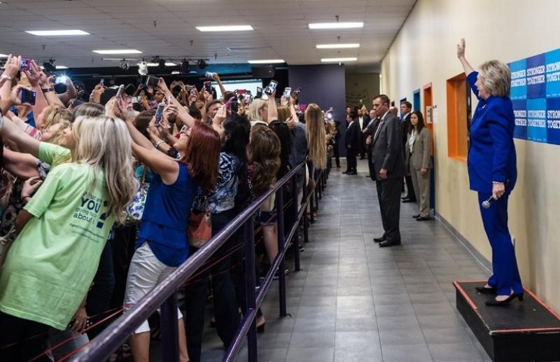 Nữ ứng viên của đảng Dân chủ đứng trên bục trong căn phòng chật kín người và đang vẫy tay chào rất thân thiện. Tuy nhiên, không ai ở phía trước bà đối mặt với bà Clinton.