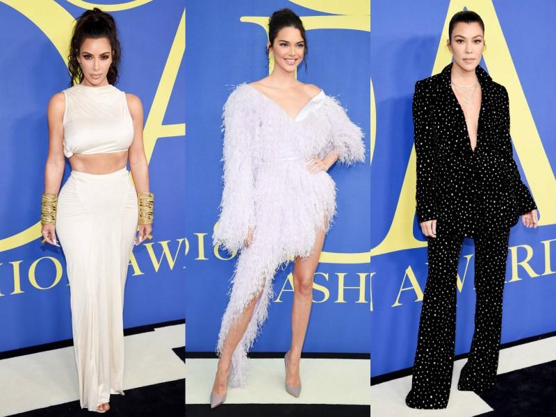 Bộ ba chị em nhà Kardashian xuất hiện với 3 phong cách khác nhau trên thảm đỏ lễ trao giải CFDA 2018. Kim Kardashian West (trái) tự tin khoe dáng đồng hồ cát quyến rũ trong thiết kế của Rick Owens. Kendall Jenner khoe chân dài miên man trong trang phục của Alexandre Vauthier cùng giày Jimmy Choo. Kourtney Kardashian mặc suits đen của NTK người Mỹ Christiano Siriano.