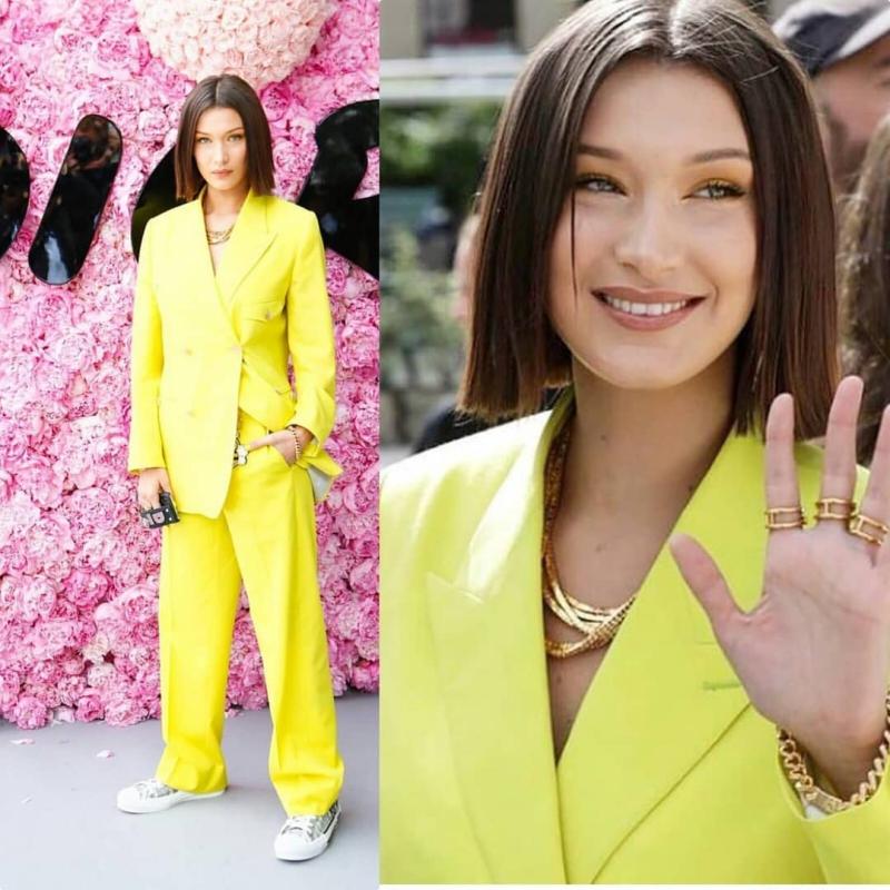 Bella Hadid mặc bộ suit màu vàng cùng giày sneakers của Dior Homme. Cô cũng đeo phụ kiện nhẫn, vòng cổ được thiết kế bởi Yoon Ambush cho Dior Homme.