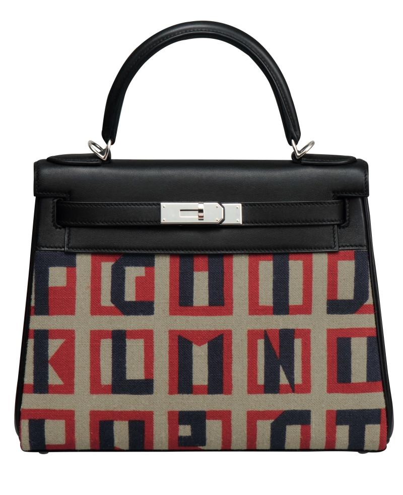 Túi Kelly Retourné cỡ 28 với các ký tự chữ cái được thiết kế bởi Mademoiselle D từ những năm 1930.  Túi làm bằng chất liệu vải và da bê Swift.