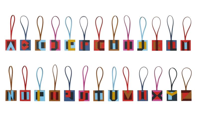 Những thiết kế chữ của Mademoiselle D được tái hiện trong những thiết kế bagcharm - phụ kiện cho túi xách vô cùng xinh xắn và nổi bật bởi màu sắc sinh động.