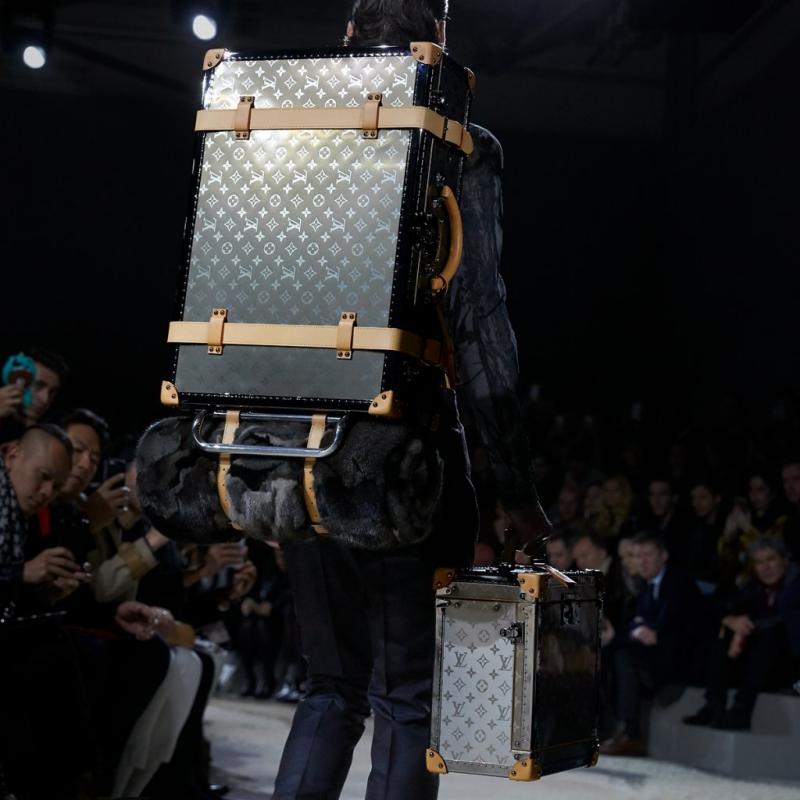 Và chính xác thì anh chàng người mẫu này đang mang theo cả một gia tài trên lưng và trên tay mình.