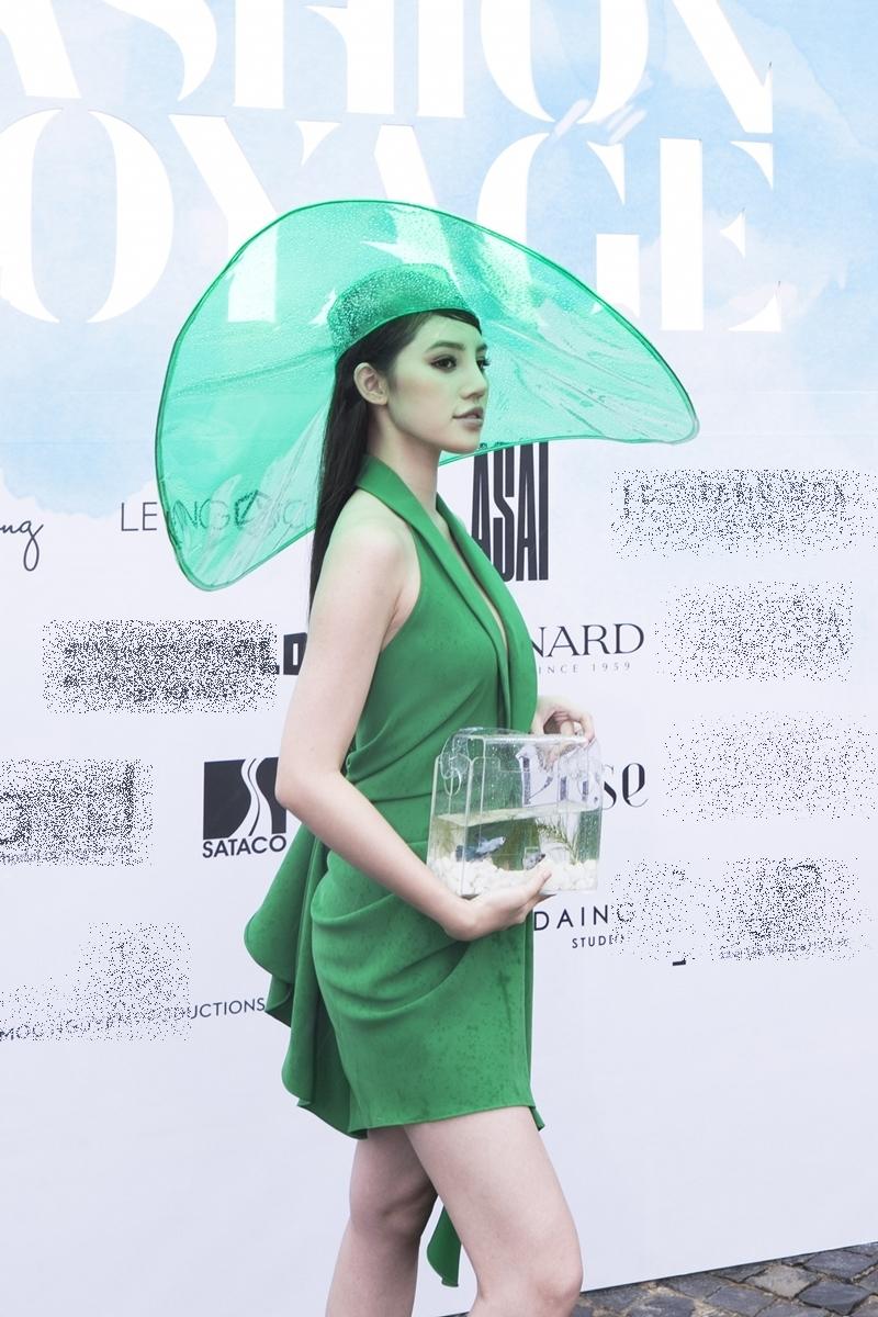 Hoa hậu Jolie Nguyễn gây ấn tượng với mũ rộng vành màu xanh lá và túi xách trong suốt.