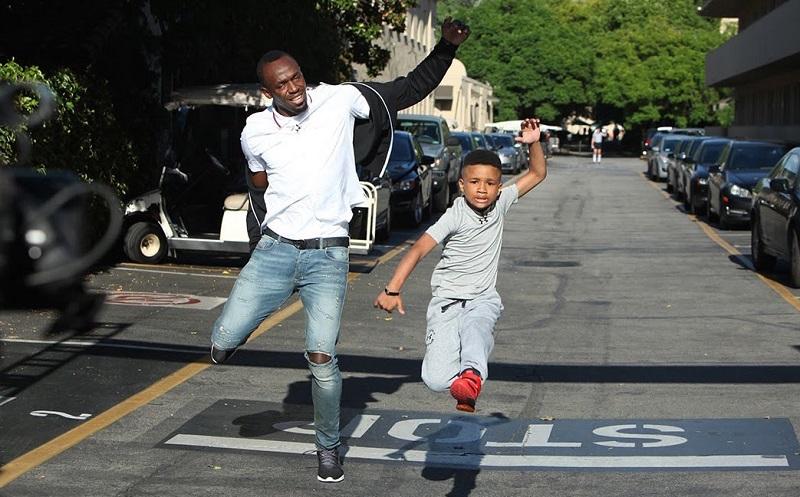 """Smith đề nghị """"tranh tài"""" cùng ngôi sao điền kinh Usain Bolt. đã có màn chạy đua thú vị với một cậu nhóc 8 tuổi, điều đặc biệt """"Người đàn ông chạy nhanh nhất thế giới đã để thua"""". Giả vờ bị thương ở chân và để thua của vận động viên người Jamaica đã để lại ấn tượng đẹp trong lòng tất cả mọi người."""