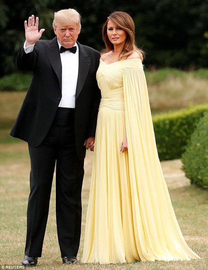 """Cuộc đổ bộ thời trang của Melania Trump tại xứ sở sương mù vẫn chưa có dấu hiệu dừng lại, khi bà và Tổng thống Mỹ tiếp tục thay đổi trang phục để chuẩn bị đến sự kiện đặc biệt tổ chức tại nơi sinh cố Thủ tướng Anh quốc - Winston Churchill ở Oxford. Nhiều trang báo còn ví von chiếc váy vàng khiến Đệ Nhất Phu nhân như nàng Belle bước ra từ truyện cổ tích """"Beauty and The Beast""""."""