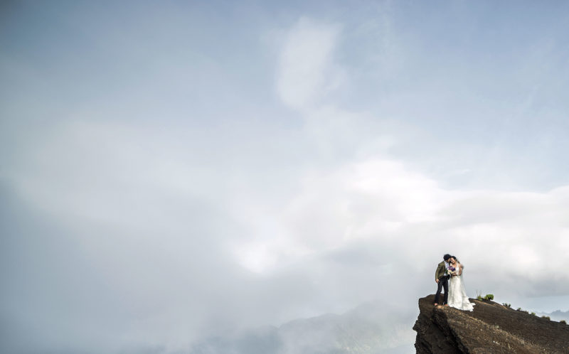 Pic by Keow Wee Loong/Caters News - (Pictured: Newly weds Wayne Huang and Amanda Tsao from Taiwan share an embrace on the 3700m peak of Mt.Rinjani, Indonesia.) - A couple on cloud nine in love braved freezing temperatures and a three day hike for a stunning wedding shoot. Photographer, Keow Wee Loong was asked by a couple in Taiwan to take the most extreme wedding photos ever and they could not have been happier with the results. Wayne Huang and Amanda Tsao contacted Keow with an idea to have their wedding photos taken on mount Rinjani, Indonesia and Kinabalu, Malaysia. SEE CATERS COPY.