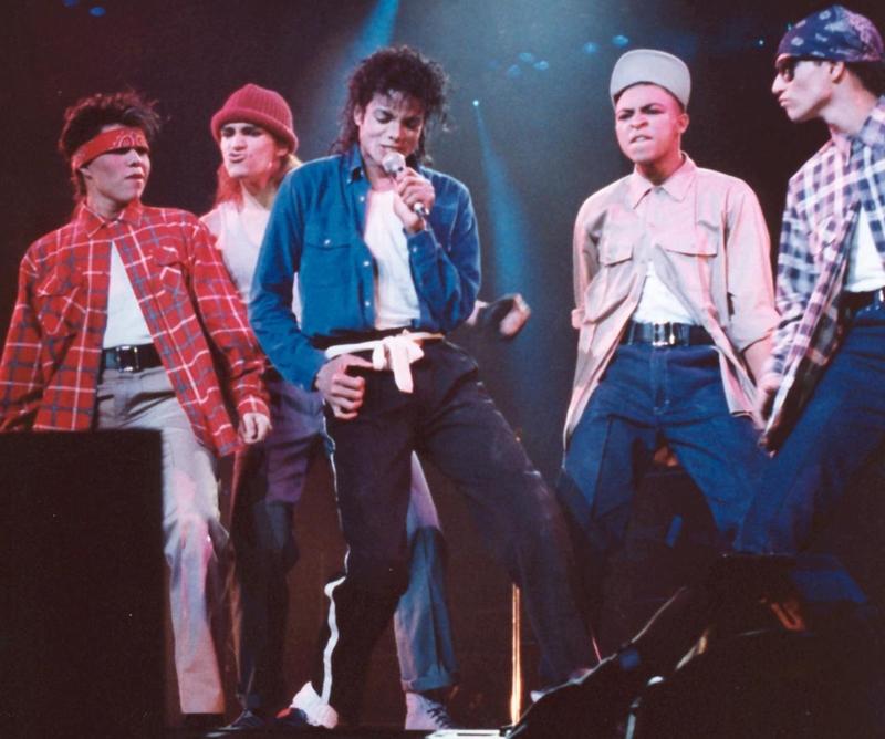 Bộ trang phục của Michael Jackson (giữa) mặc trong đêm diễn đó gồm: áo thun trắng, áo sơ mi khoác hờ màu xanh biển và chiếc quần ống suông có đường kẻ sọc trắng.
