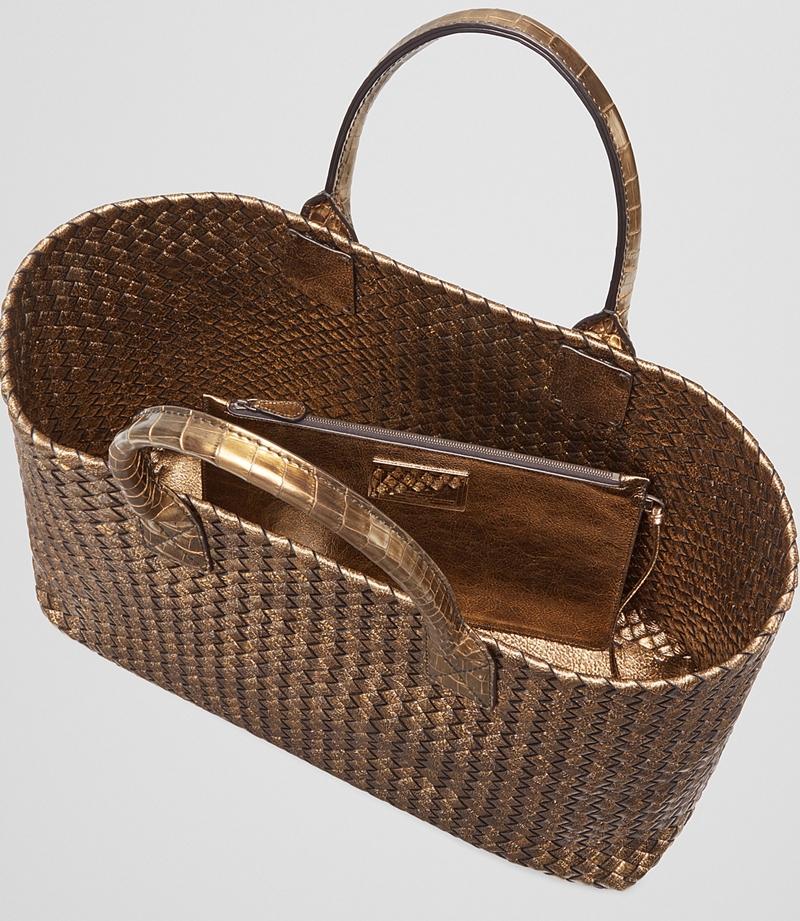 Đi kèm với túi xách là một chiếc ví cầm tay hình chữ nhật nhỏ gọn, cùng tông vàng ánh kim.
