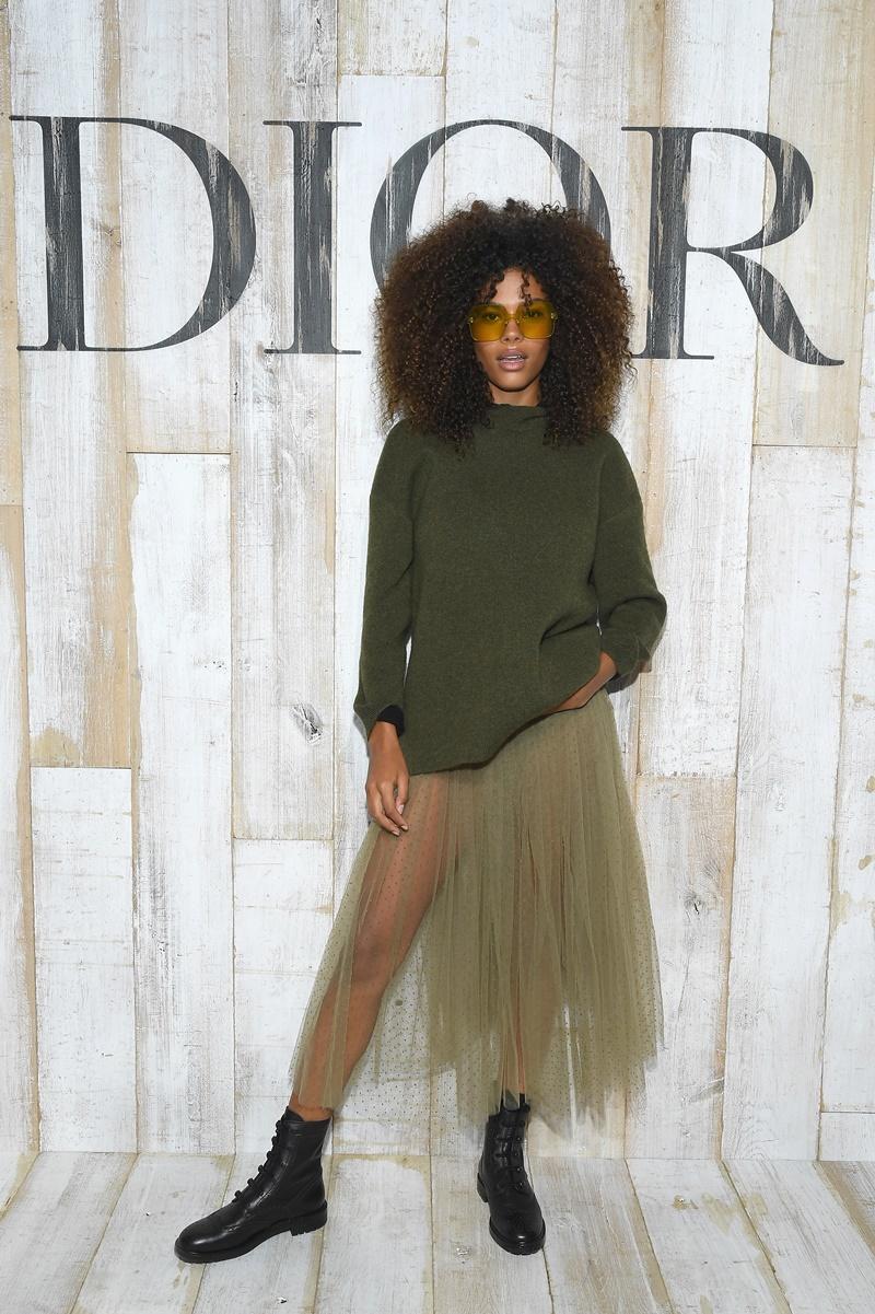 Nàng mẫu da màu đình đám Tina Kunakey mặc trang phục cá tính của Dior cùng cặp kính DiorColorQuake màu xanh lá cây.