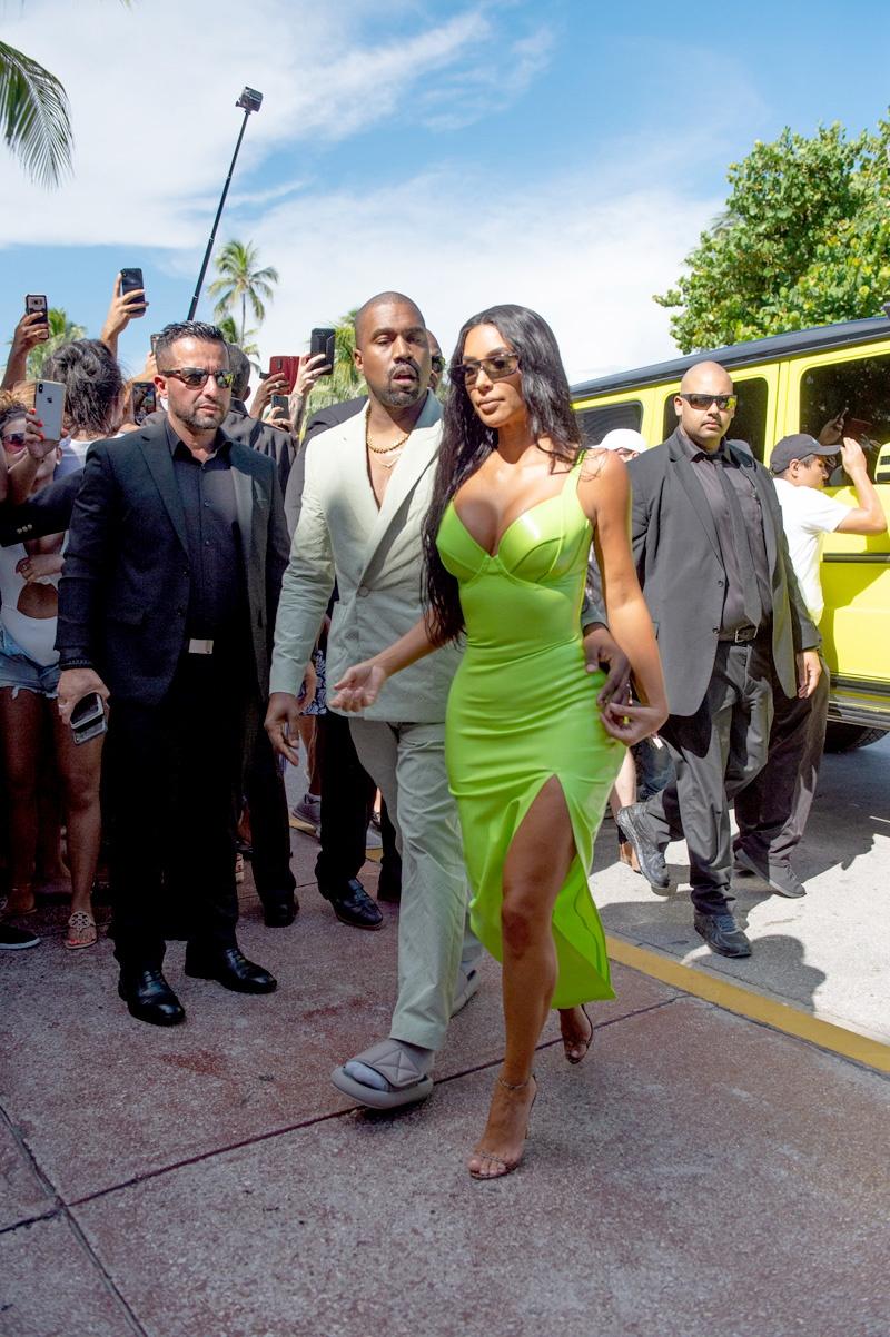 """Kim Kardashian West cùng ông xã Kanye West xuất hiện tại đám cưới của rapper 2 Chainz ở Miami, Mỹ vừa qua. Cô nàng """"siêu vòng ba"""" chọn mặc thiết kế đầm latex màu neon cực kỳ bắt mắt."""
