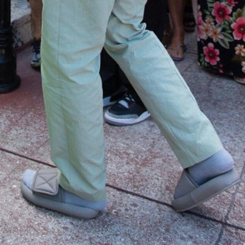 Trong khi cô vợ nổi bần bật với thiết kế đầm neon xẻ đùi gợi cảm thì Kanye West lại gây nhíu mày khi anh chọn phối một đôi dép lê của thương hiệu Yeezy cùng bộ suit lịch lãm của Louis Vuitton.
