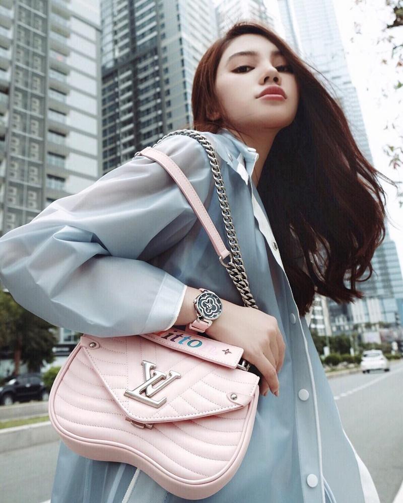 Jolie Nguyễn rút gọn quai đeo để túi nằm gọn gàng bên cạnh mình.