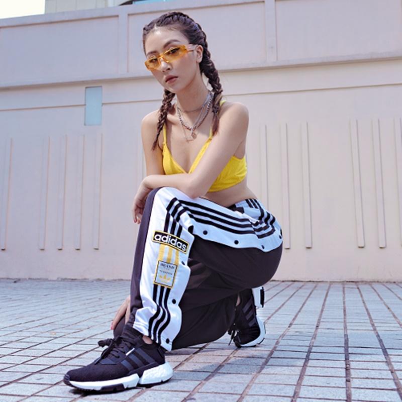 Một hình ảnh phá cách của Quỳnh Anh Shyn với chiếc quàn cài khuy dọc hai bên ống của adidas và áo top màu vàng tiệp màu cặp kính.