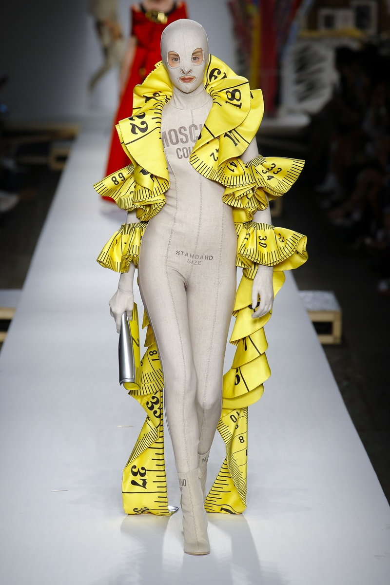 """Là """"kẻ mộng mơ"""" của sàn diễn nước Ý, Moschino vẫn tiếp tục gây ấn tượng bởi các thiết kế mang hơi hướng avant-garde như mẫu bodysuit có áo choàng mô phỏng dây thước của thợ may này đây."""
