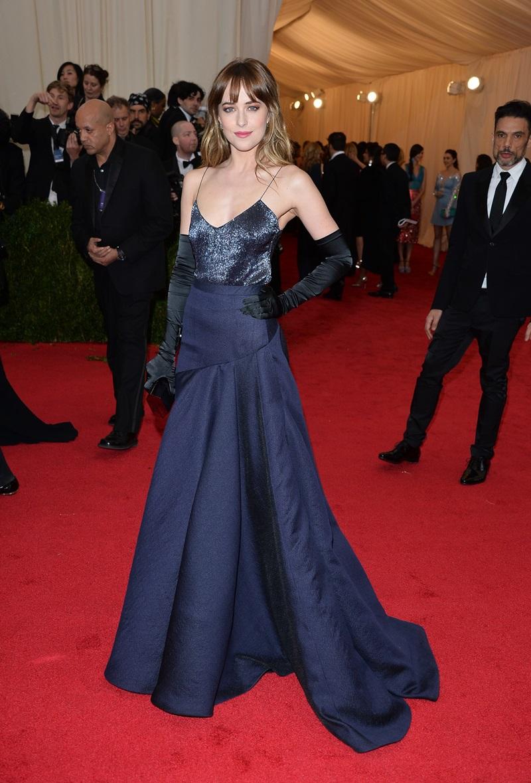 """Ở một diễn biến khác, nữ chính """"50 sắc thái"""" - Dakota Johnson tuy cũng từng diện váy với găng tay lên thảm đỏ nhưng nhờ biết cách phối màu sắc hài hòa mà Dakota gây ấn tượng bởi vẻ ngoài hết sức gợi cảm nhưng không kém phần sang trọng của mình."""