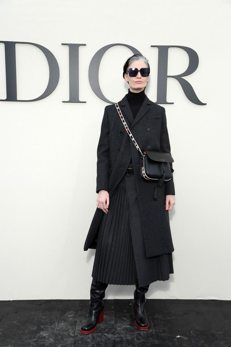 Siêu mẫu Erin O'Connor siêu ngầu với bộ trang phục đen, có điểm nhấn là phần đế boots màu đỏ và dây đeo túi xách ánh kim, cùng một cặp kính mát Diorcolorquake sắc đen sành điệu.