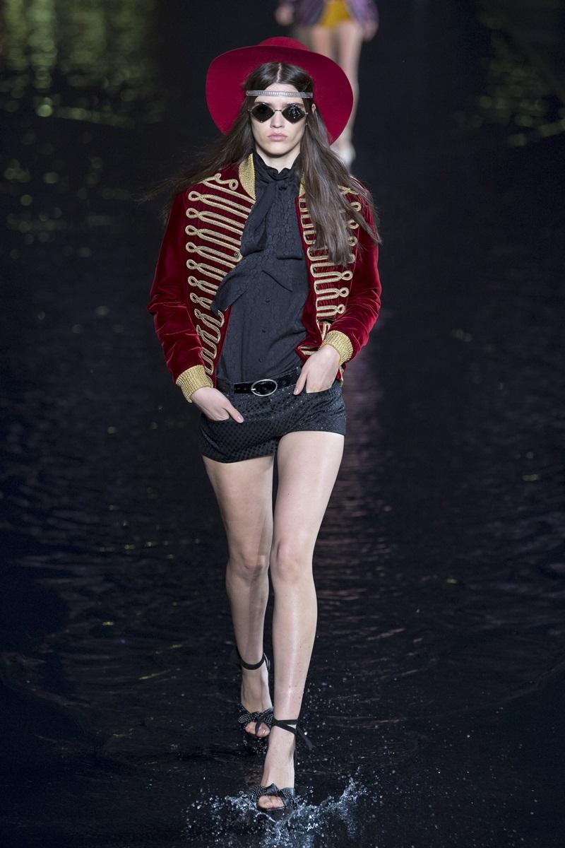 Kiểu áo khoác quân đội tông đỏ kết hợp đường chỉ thêu màu vàng của thập niên 70 và 80 tạo sự thú vị khi góp mặt trên sàn diễn cùng áo sơ-mi và quần short đen.