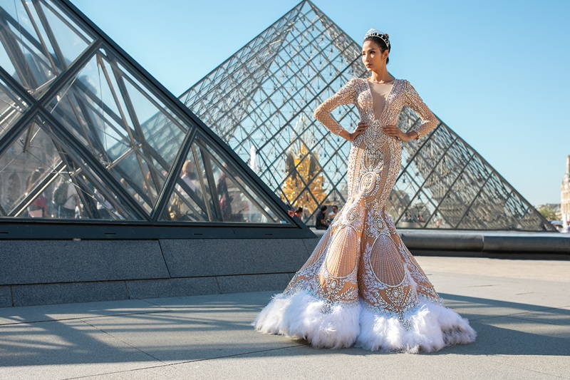 """Giữa ánh nắng vàng rực của mùa Thu tại Paris, những hạt đá quý gắn kết trên váy càng trở nên lóng lánh hơn. Đặc biệt, các đường may và xếp pli gấp khúc được thể hiện khá tỉ mỉ, giúp Á hậu Hoàng Thùy thể hiện hình ảnh của một """"nàng tiên"""" kiêu sa, lộng lẫy."""