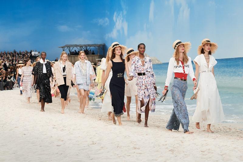 Những người mẫu đi chân trần trên cát và nô đùa cùng sóng biển.