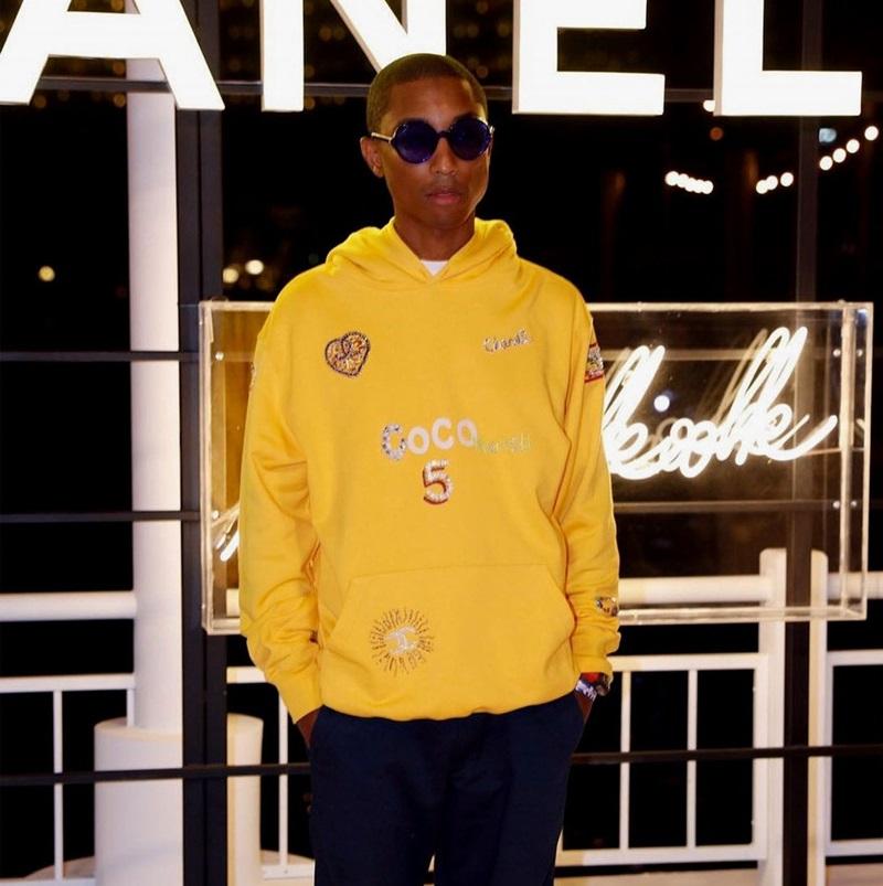 """Xuất hiện tại show diễn, Pharrell diện một chiếc áo hoodie tông vàng rực với những chi tiết điểm xuyết trên đó như biểu tượng """"double C"""", dòng chữ Coco, hình trái tim màu ánh kim,... mà theo như Chanel tiết lộ thì đây chính là thiết kế trong BST mới của nhà mốt này và Pharrell Williams."""