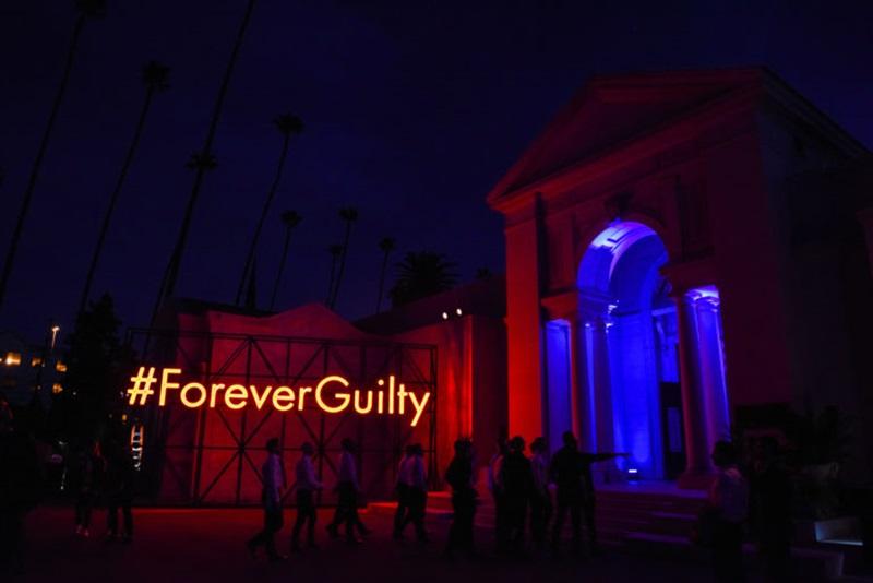 Khuôn viên nghĩa trang Hollywood Forever với ánh sáng neon đủ màu sắc, cùng dòng chữ đề tên của bữa tiệc vô cùng nổi bật #ForeverGuilty.
