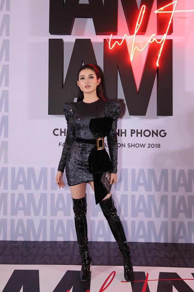 Á hậu Huyền My chọn một thiết kế đầm mini dài tay đính sequin phối cùng boots da bóng cao quá gối. Điểm nhấn của trang phục là chi tiết nơ bằng nhung đính bên hông.