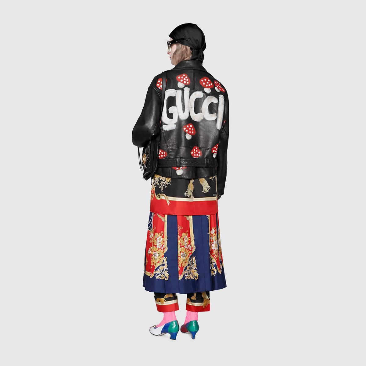 Phía sau chiếc áo có in những họa tiết cây nấm và dòng chữ Gucci.