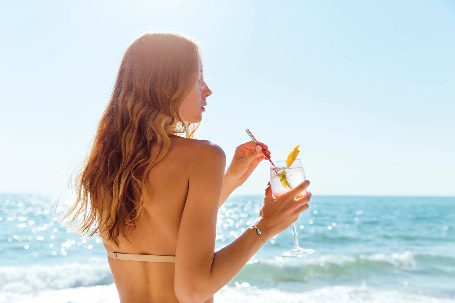 Back view of woman with cocktail, against the sea background