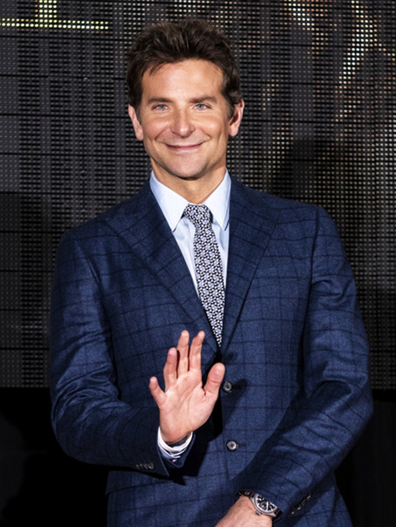 Cho đến khi, Bradley Cooper cởi áo khoác và để lộ ra bên trong là bộ suit kẻ caro màu xanh navy. Nhưng điều khiến mọi người chú ý lại chính là chiếc nút dưới của áo vest.