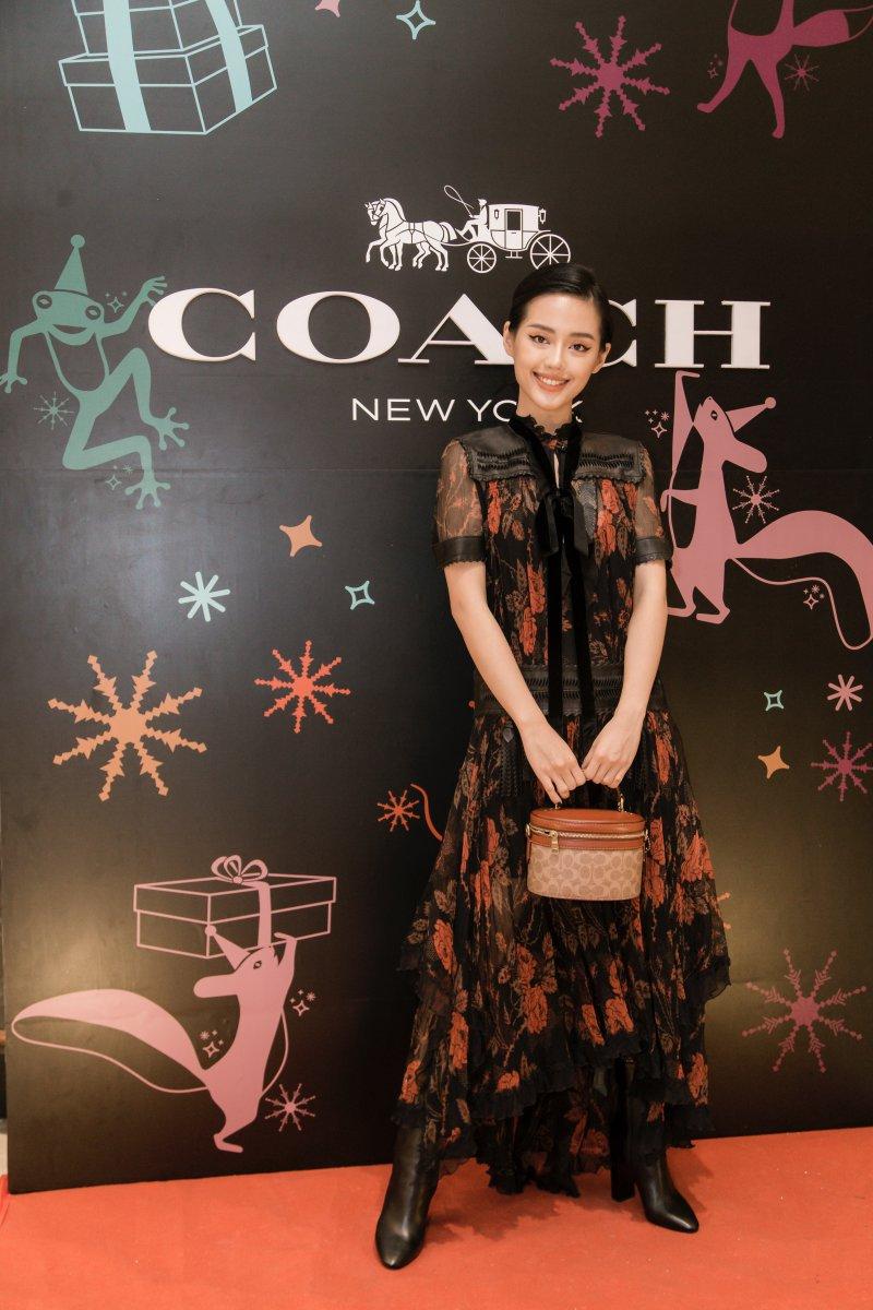 Khánh Linh chọn mặc thiết kế đầm dài với những họa tiết nổi bật và trẻ trung. Cô phối cùng túi xách Trail xinh xắn là phụ kiện tiêu biểu trong BST mới của Coach.