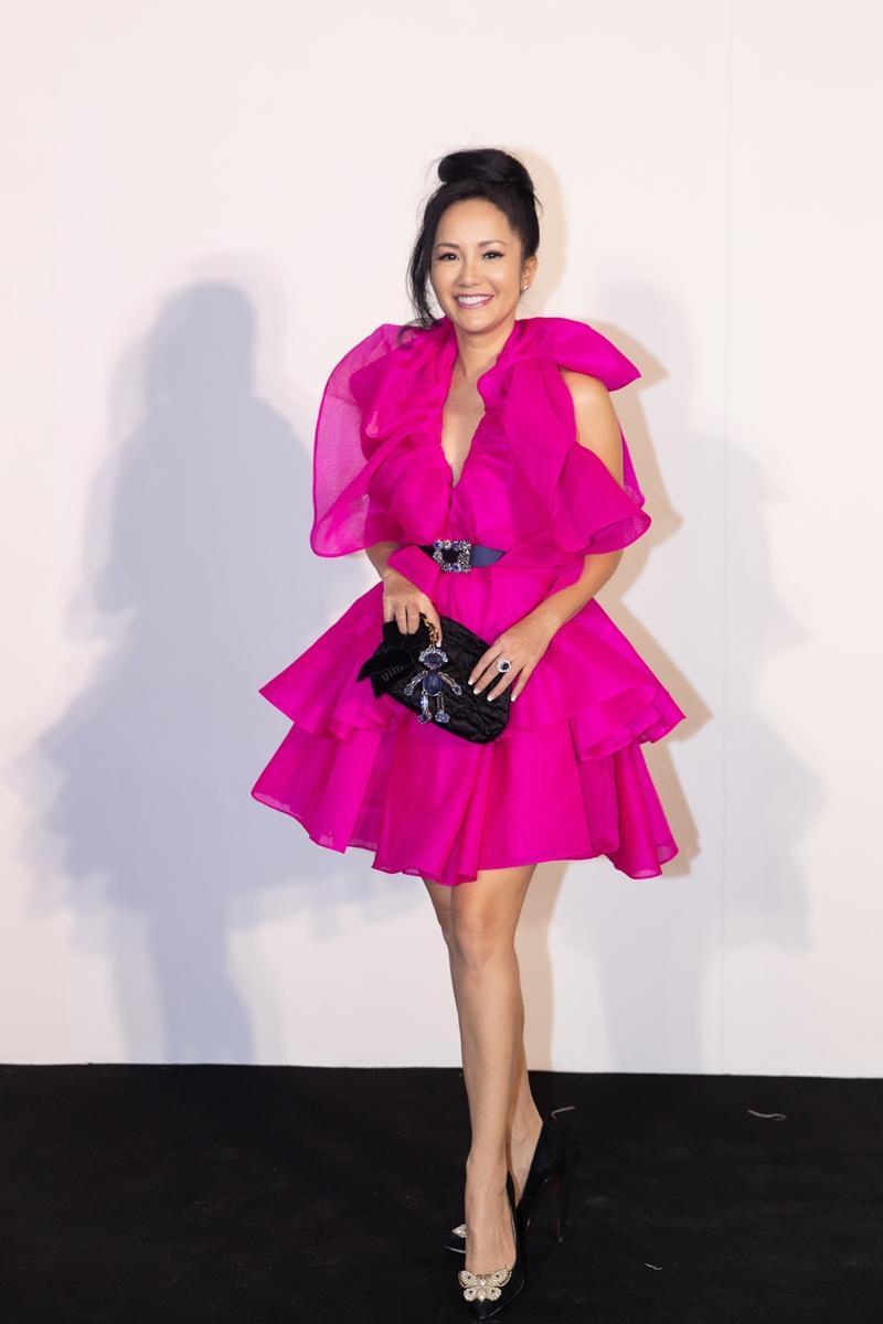 Diva Hồng Nhung trẻ trung với thiết kế màu hồng rực rỡ với những đường nét mềm mại, bay bổng. Nữ ca sĩ chọn phụ kiện màu đen để dung hoà sắc độ trang phục.
