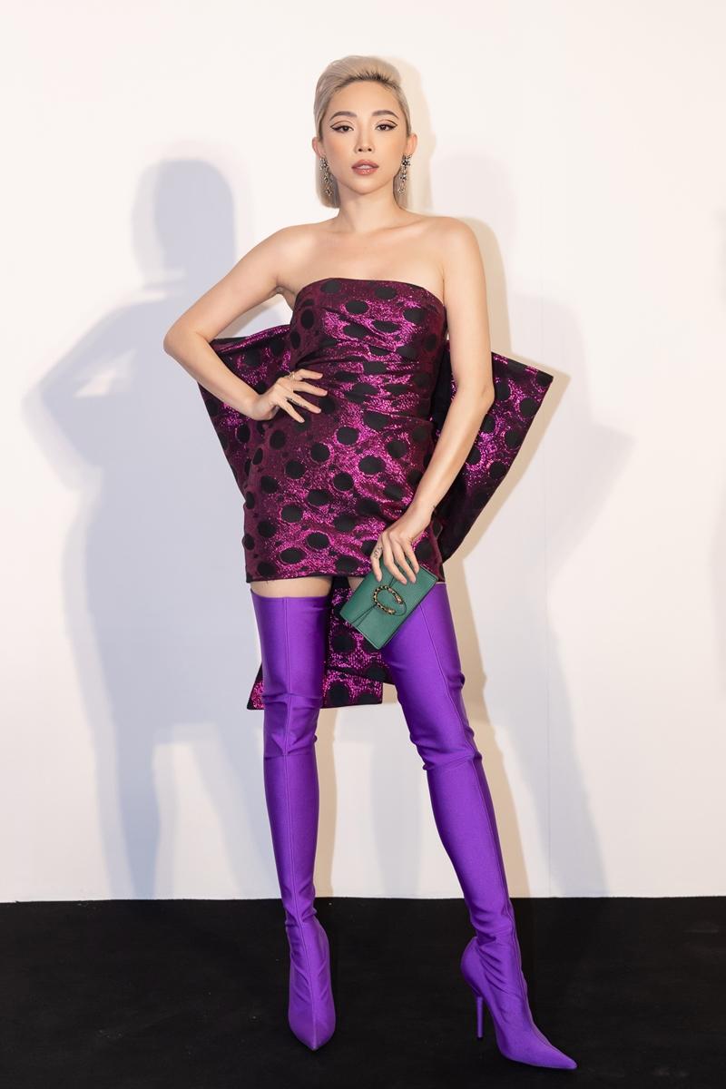 Tóc Tiên gợi cảm, cá tính với chiếc đầm cúp ngực, dài trên gối phối cùng boot tím đặc sắc của Balenciaga cùng ví cầm tay màu xanh của Gucci.