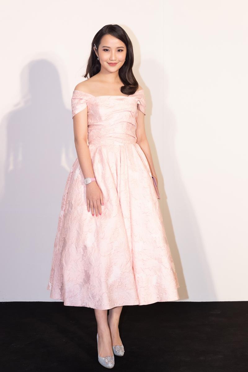 Trương Minh Xuân Thảo dịu dàng, đằm thắm với chiếc váy xoè màu hồng có hoạ tiết to bản. Cô kết hợp thiết kế cùng hoa tai nhỏ xinh, đồng hồ đeo tay sang trọng.