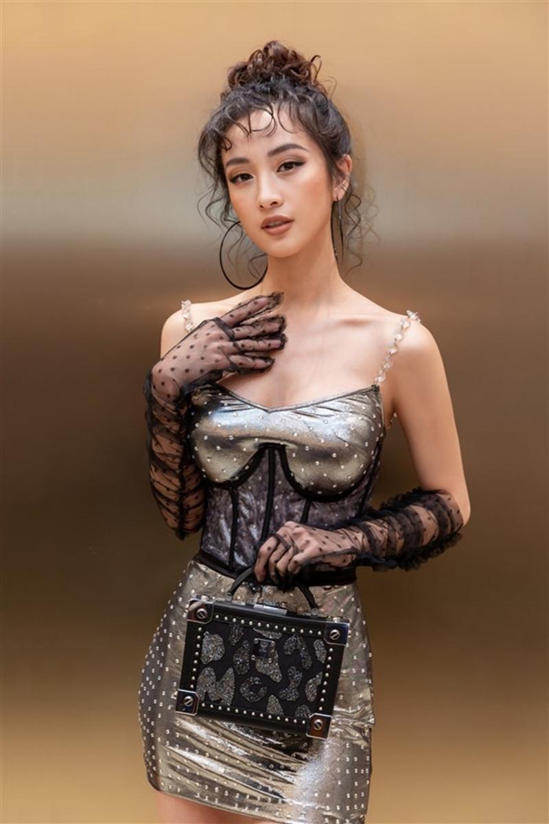 Cô chọn một chiếc túi xách phom cứng của MCM tạo điểm nhấn cho trang phục của mình.