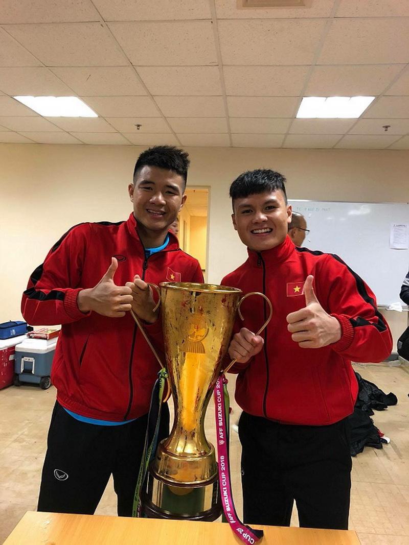 Quang Hải và Đức Chinh chụp kỉ niệm cùng cúp vô địch