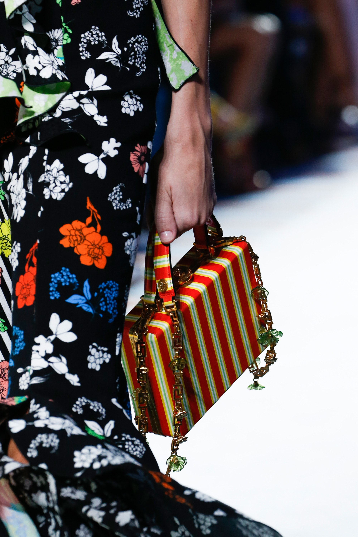 Cùng chiếc túi xách hộp với quai xích xen kẽ những họa tiết đặc thù của Versace.