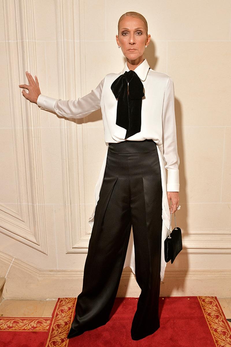 """Cùng ngày 22/01, Celine Dion tiếp tục khoác lên người bộ cánh thứ 2, có phong cách gần như """"trái dấu"""" hoàn toàn so với chiếc đầm sắc sảo trước đó. tại show diễn Armani Privé, nữ ca sĩ toát lên nét mạnh mẽ, cá tính cùng kiểu trang phục menswear gồm áo sơ-mi trắng thắt nơ mix cùng quần đen cạp cao."""