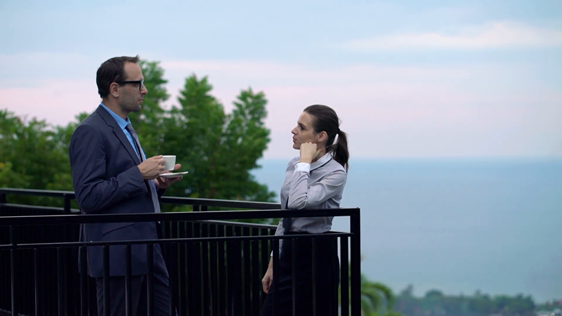 business-couple-chatting-and-drinking-coffee-on-terrace_vkgxmvp5f__f0000