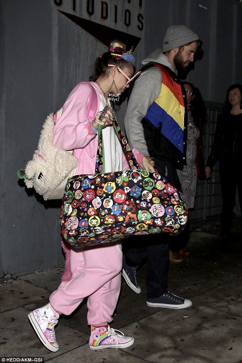 Mặc đồ hóa trang đã đành, Miley còn đầu tư thêm phụ kiện với kính mắt hình que kem, dây chuyền gắn chữ, đầu đồi vương niệm lấp lánh. Ngoài ra, Miley còn đeo balo hình con thỏ kèm theo túi xách chi chít sticker động vật ngộ nghĩnh bên ngoài và đôi giày thể thao cũng được cô nàng lựa chọn với đủ sắc cầu vồng.