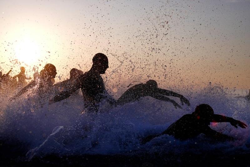 Bức ảnh là khoảng khắc đắt giá và đẹp chất ngất khi con người hòa mình vào thiên nhiên được lưu lại tại đường đua Ironman ở Barcelona vào ngày 20/5/2018. Trong ánh nắng vàng, hàng loạt chiếc bóng uốn mình, lượn theo sóng nước trên mặt nước biển. Đây là thời điểm họ chạy nước rút xuống biển với tốc độ tối đa.