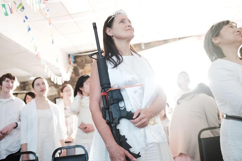 """Bức ảnh người phụ nữ đang giương cao khẩu súng trường tại một buổi lễ cam kết của người Hồi giáo được chụp lại tại Pennsylvania chỉ sau 1 tuần xảy ra vụ xả súng tại trường trung học Marjory Stoneman Douglas ở Parkland, bang Florida, Mỹ vào ngày 14/2. Nhìn những khẩu súng tương tự đã gây ra hàng loạt cái chết thương tâm được """"vinh dự"""" có mặt trong một lễ kĩ niệm không khỏi khiến người ta chạnh lòng."""
