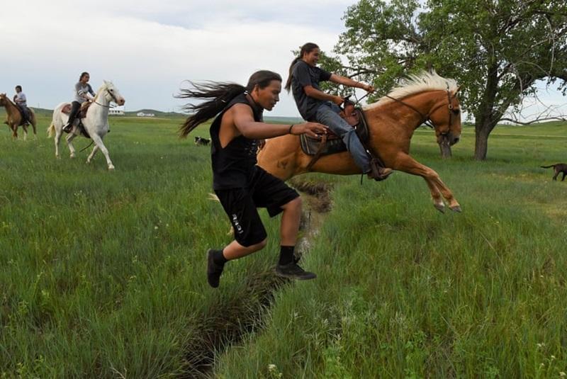 """Một cuộc đua ngựa 400 dặm từ Nam Dakota đến Fort Laramie đã được diễn ra để kỷ niệm 150 năm Hiệp định bảo vệ quyền lợi của xứ Sioux – vùng đất của người Mỹ bản địa. Nhìn nét mặt vui vẻ cùng sự phấn khích của các thanh niên trẻ nơi đây khiến người ta không khỏi chạnh lòng về một trong những sắc dân nghèo nhất nước Mỹ sắp """"tuyệt chủng""""."""