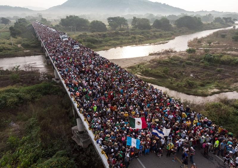 """Trong hình là đoàn người di cư Honduras (với số thành viên ước tính lên đến 7.000 người) trên cây cầu biên giới Guatemala ở Ciudad Hidalgo, bang Chiapas, Mexico vào ngày 20/10. Đây là khoảnh khắc tiêu biểu của năm 2018, khắc họa """"cuộc hành trình đau đớn nhất"""" khi niềm hy vọng được đáp đền lại bằng những hoài nghi. Họ rời khỏi Trung Mỹ để tìm kiếm sự an toàn thì nhà cầm quyền Hoa Kỳ lại dán mác họ là quân """"xâm lược""""."""