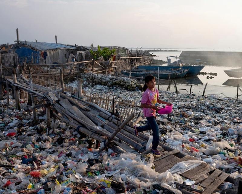 """Hòn đảo Panggang nằm ở phía bắc Jakarta là một nơi tập trung những khu nhà nổi và chợ. Hậu quả của việc người dân không có giải pháp """"sống xanh"""" cùng môi trường là không còn nơi nào cho người và hẳn nhiên cho cả rác. Cái nhìn trong trẻo và nụ cười vô âu lo của bé gái trước quang cảnh """"quá đỗi quen thuộc và bình thường"""" này khiến người ta không khỏi xót xa."""