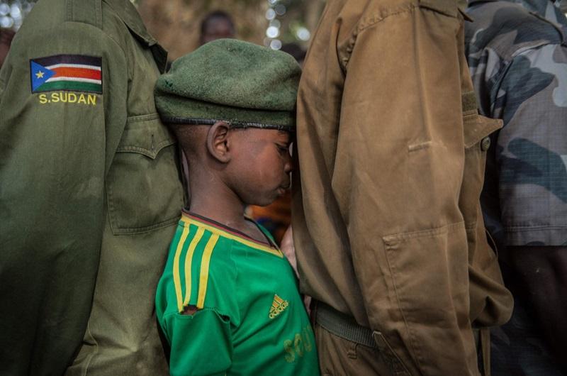 """Ở những vùng đất khỏi lửa ngập trời như Nam Sudan thì việc """"ép buộc trẻ em đi lính"""" được xem là một chiến thuật phổ biến. Bức ả̀nh được chụp trong buổi lễ mừng xuất ngũ dành cho những """"chiến binh nhí"""" tại chiến trường quân sự ở Yambio, Nam Sudan. Cậu bé đứng lọt thỏm trong hàng ngũ chiến binh chỉ mới 9 tuổi, tâm sự rằng điều mong muốn nhất là được ở bên cạnh gia đình."""