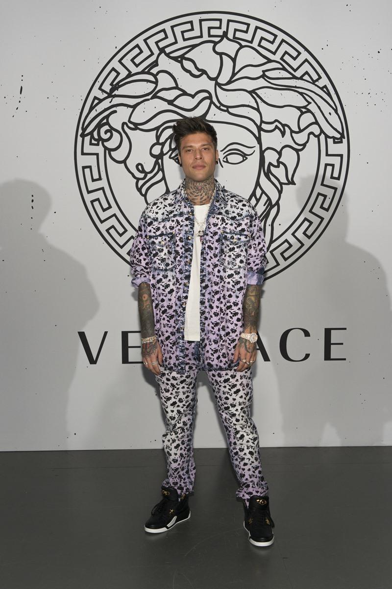 Rapper Fedez mặc trang phục denim mài bạc với họa tiết hoa lá phối cùng giày sneakers da màu đen.