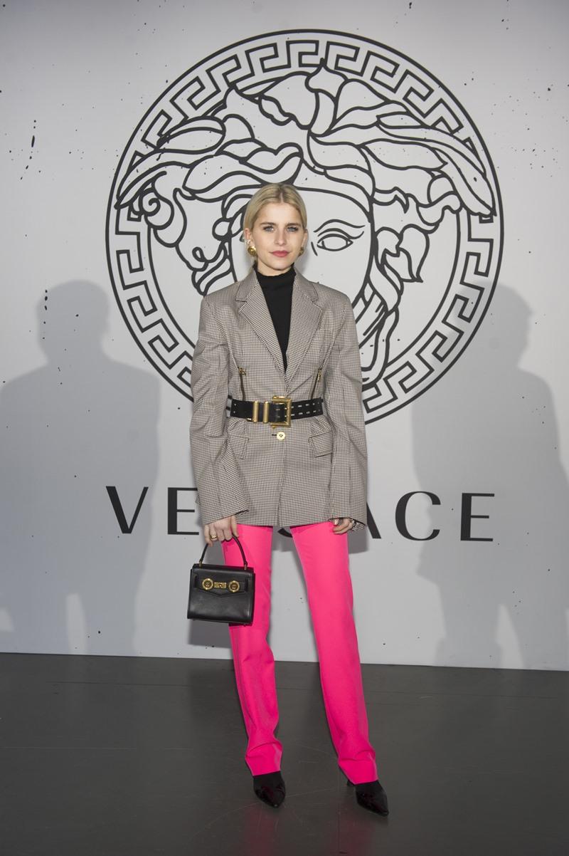 Fashionista Caroline Daur hóa thân thành quý cô cổ điển với áo cổ lọ đen và áo khoác màu trung tính, phối cùng quần màu hồng neon rực rỡ.