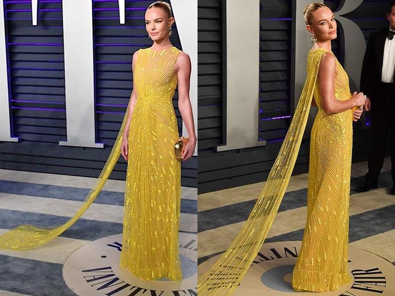 Thiết kế màu vàng rực có điểm nhấn là nếp gấp tinh tế ở phần eo và một bên vai có dải áo choàng thêm nét thướt tha cho thiết kế.