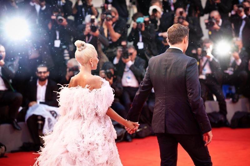 """Nhưng sự ăn ý tưởng chỉ có ở những diễn viên lành nghề đó sẽ chẳng có gì thêm ầm ĩ nếu bước ra ngoài màn ảnh, Gaga và Bradley vẫn giữ sự thân mật khó lý giải đó. Bao lần, người ta thấy cả hai đường hoàng nắm chặt tay từ thảm đỏ đến trên sân khấu trên thảm đỏ hay luôn dịu dàng nhìn nhau dù hát ca khúc """"Shallow"""" đến hàng chục lần. Những điều ấy khiến người hoài nghi, vì yêu nhau chẳng phải là không để một giây phút nào của đối phương rơi khỏi tầm mắt?"""